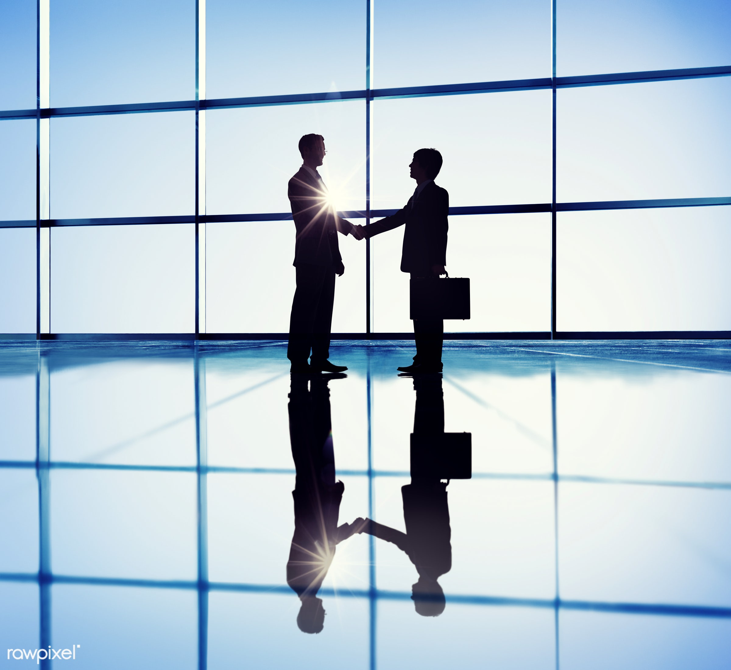Business partners shaking hands - meeting, handshake, contract, office, agreement, back lit, blue, building interior,...