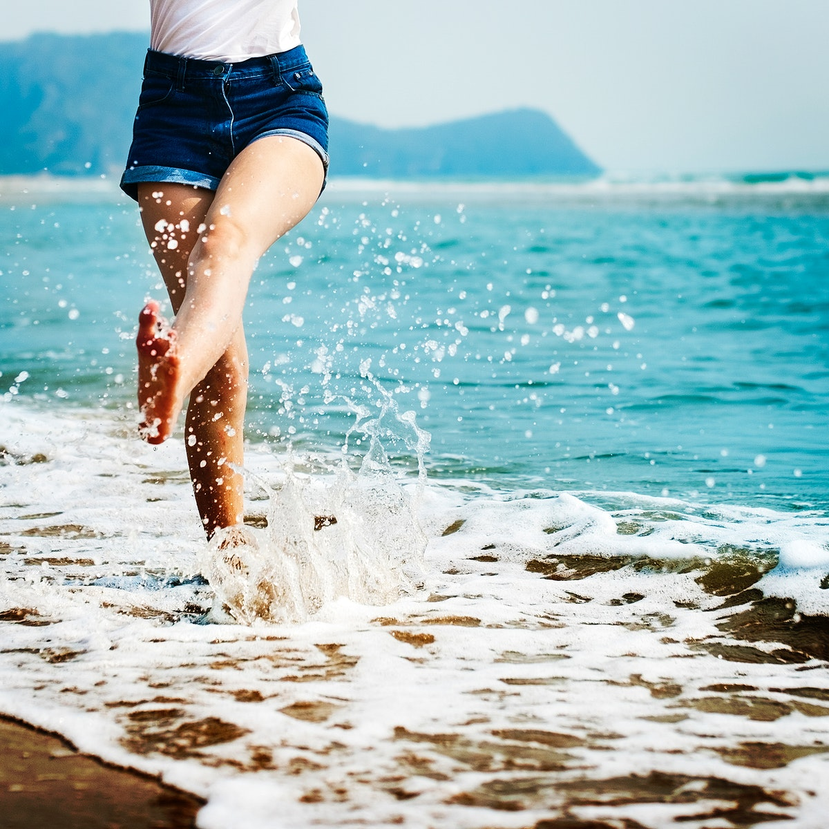 Woman feet splashing sea water