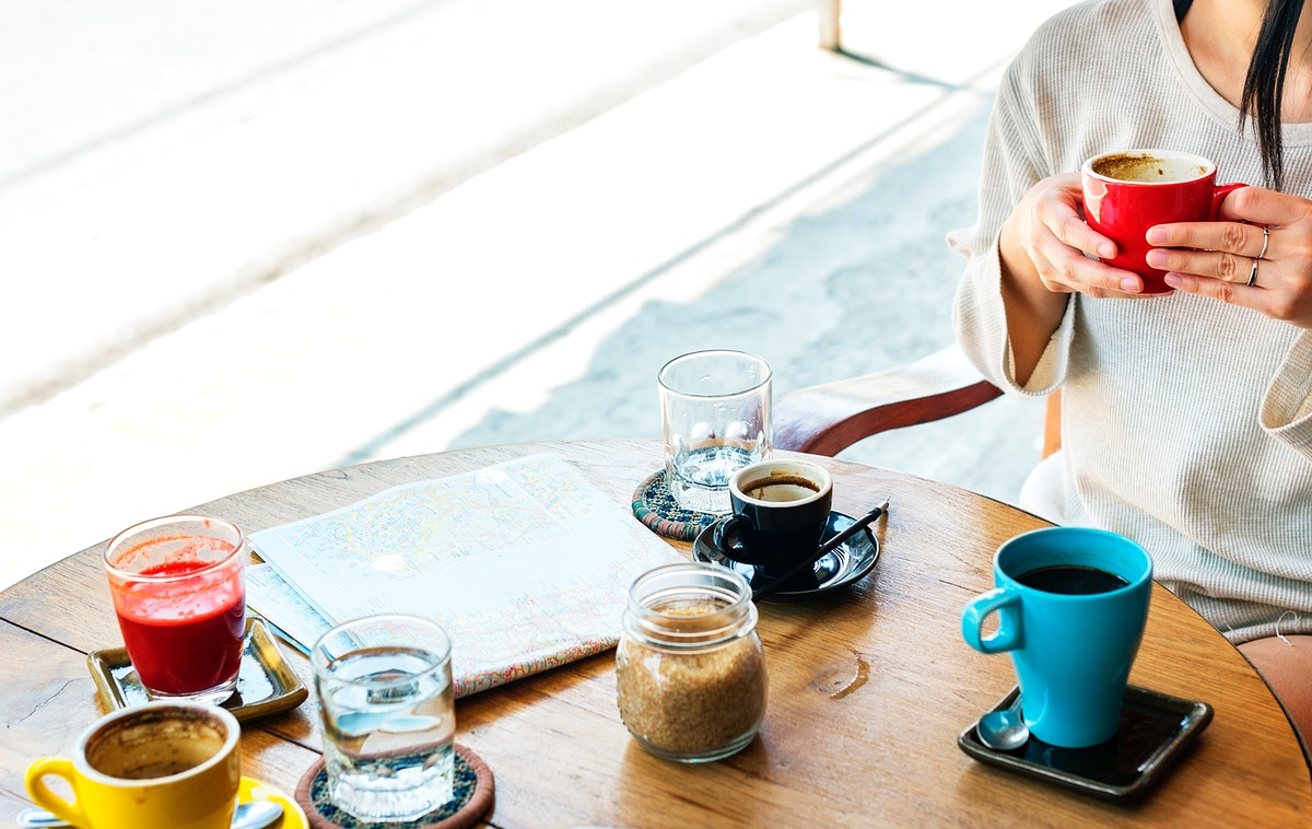 Woman sitting in coffee cafe with map on wooden table