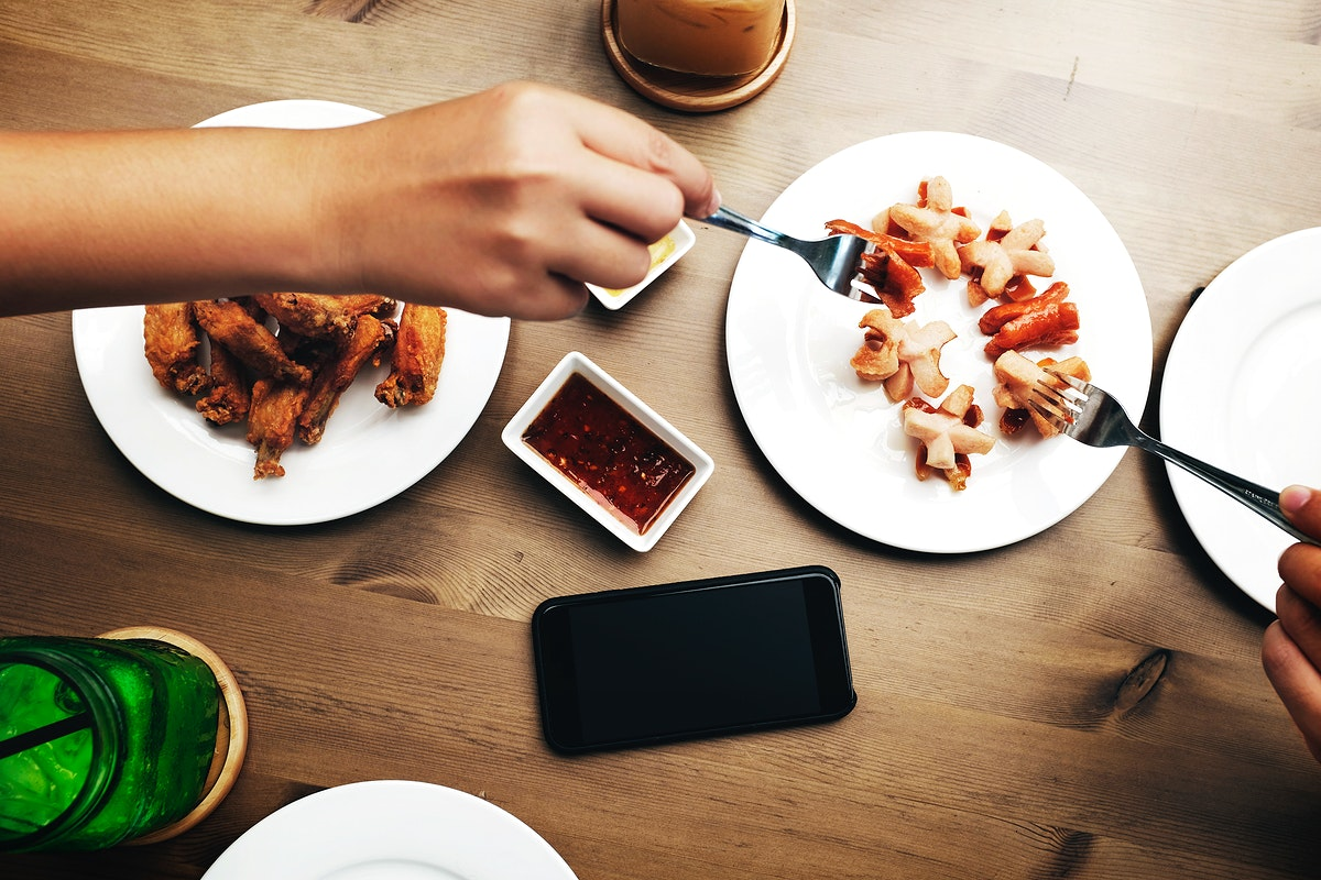 Aerial view of hands getting food on wooden table