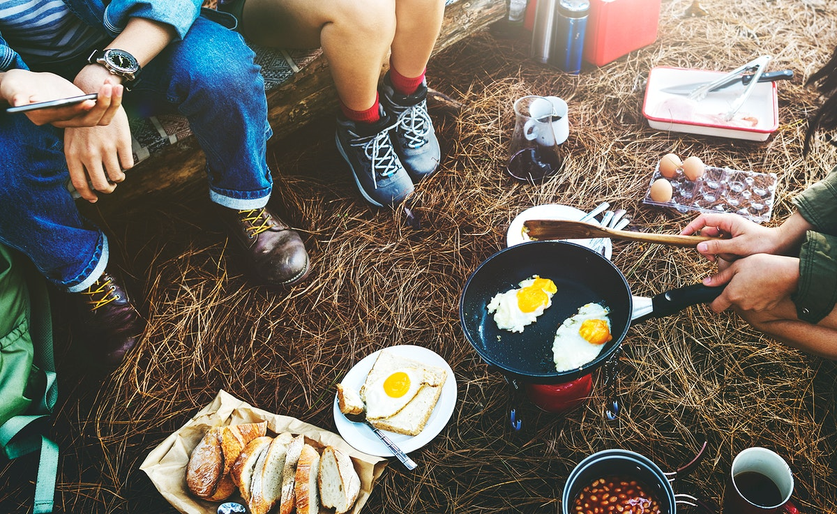 Group of friends camping together cooking food