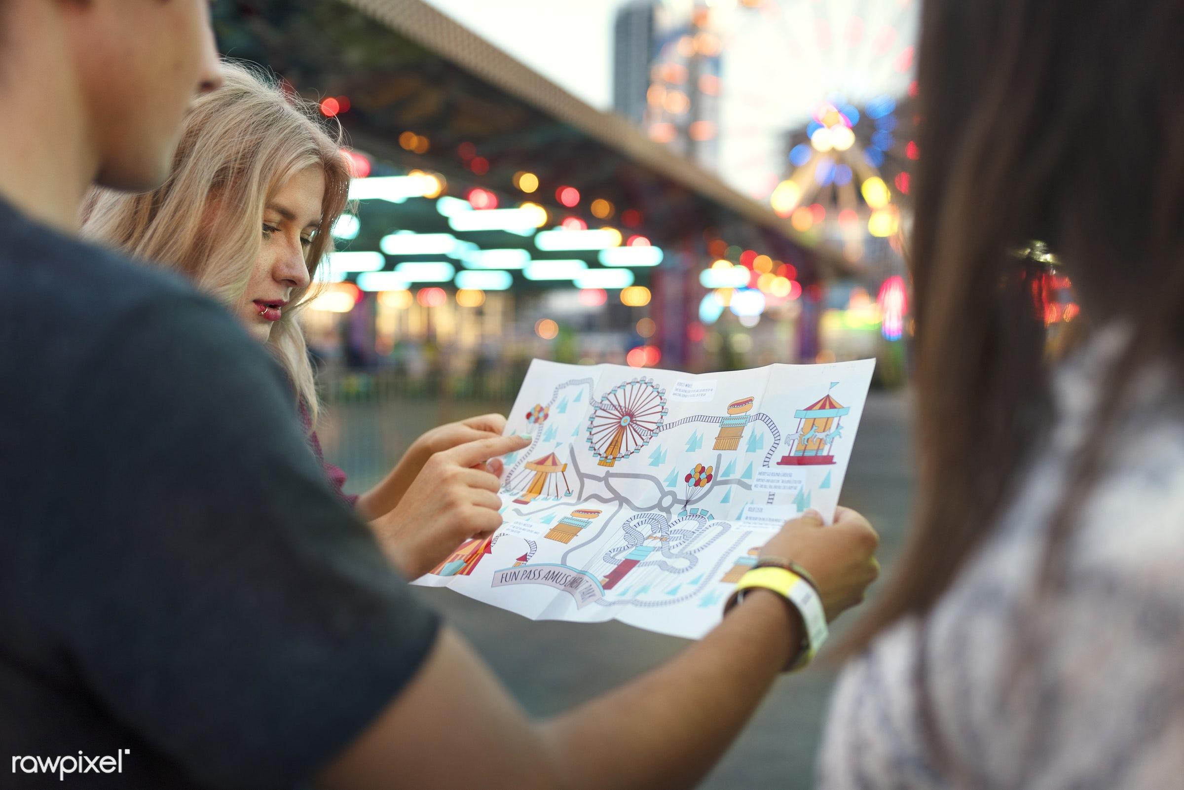 A group of friends is enjoying the amusement park - direction, amusement park, enjoyment, expression, feeling, friends,...