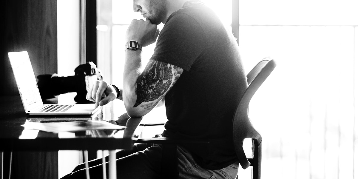 Man sitting working on laptop grayscale