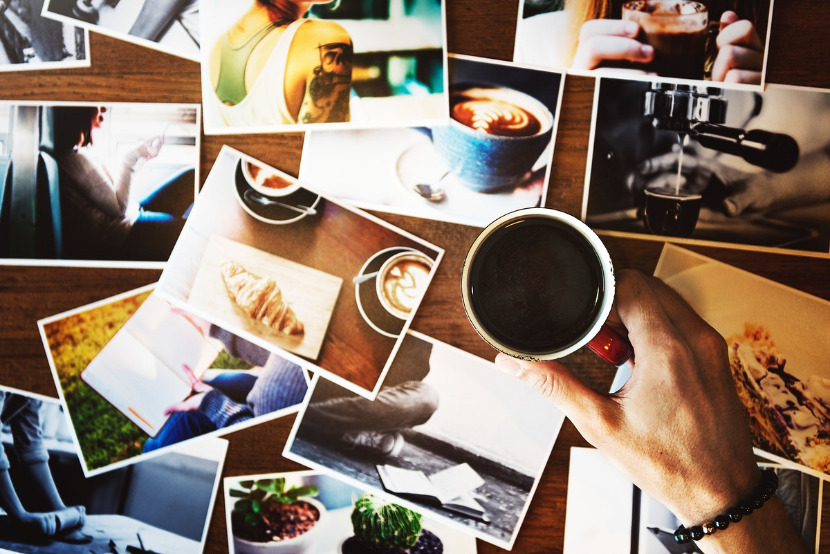 Hand holding coffee cup with may photograph on the table