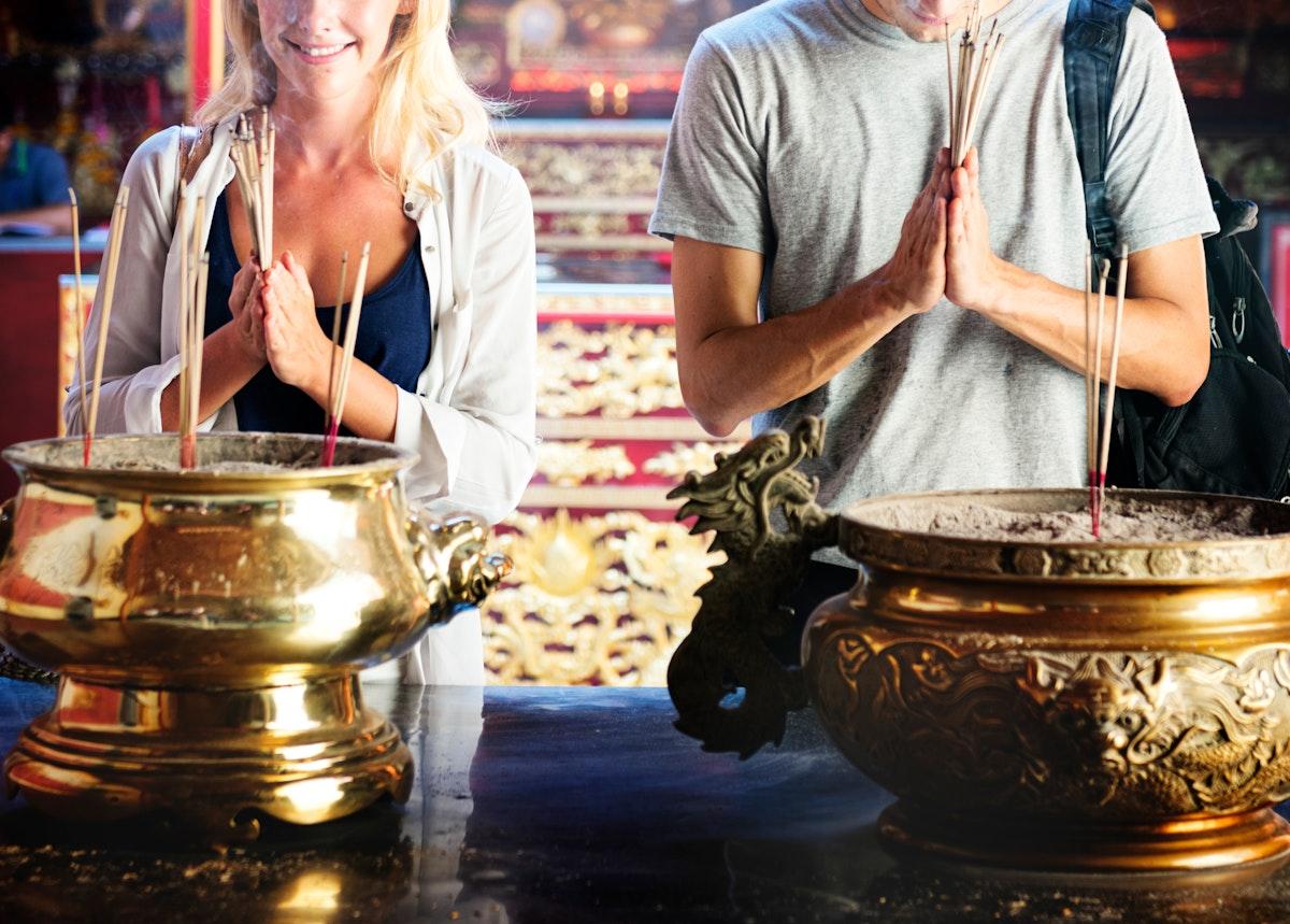 Closeup of couple with joss sticks shrine