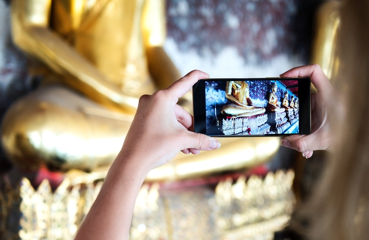 Tourist taking buddha statues by mobile phone