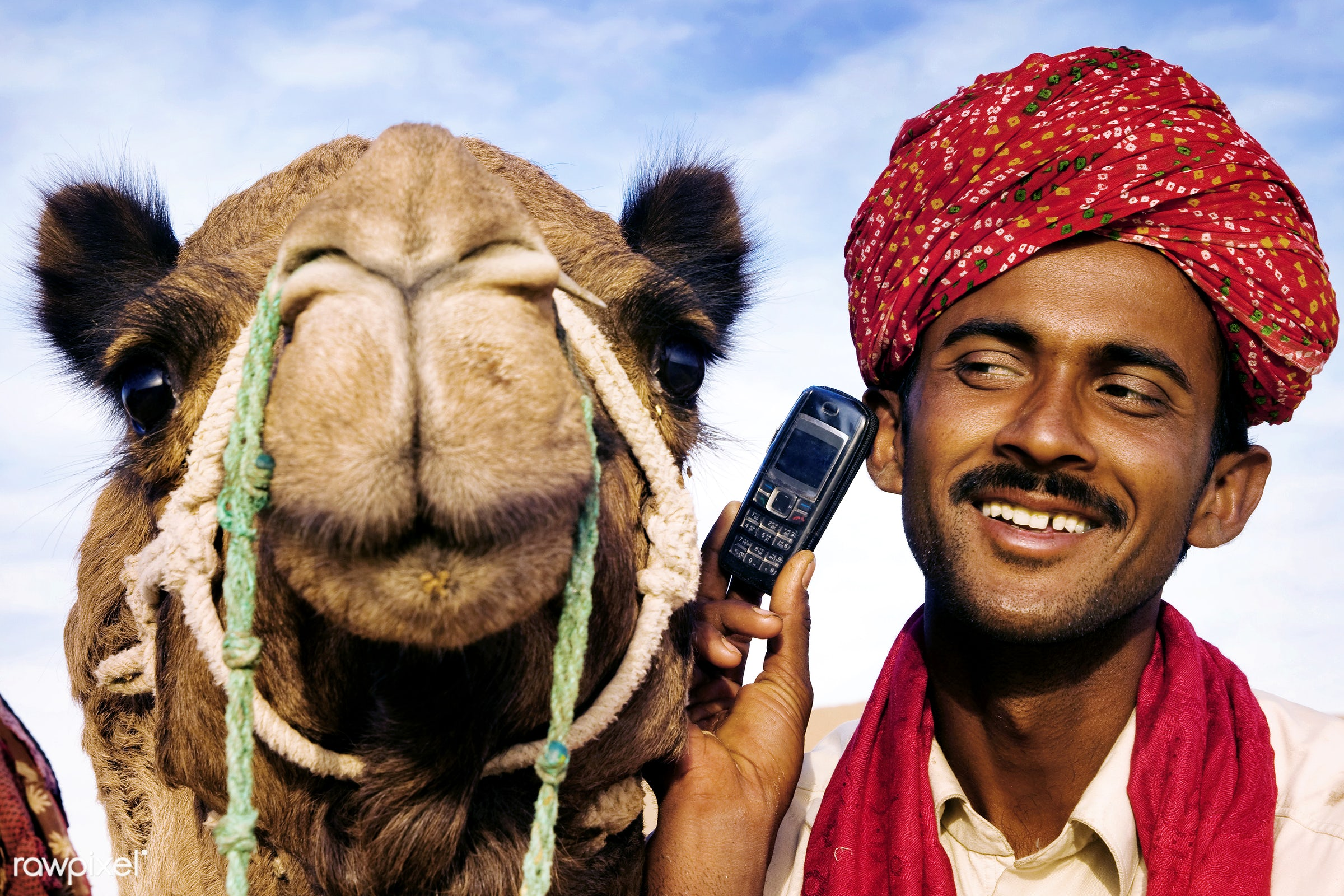 Indian man with camel talking on the phone - desert, adult, asia, business, camel, cell phone, communication, destinations,...