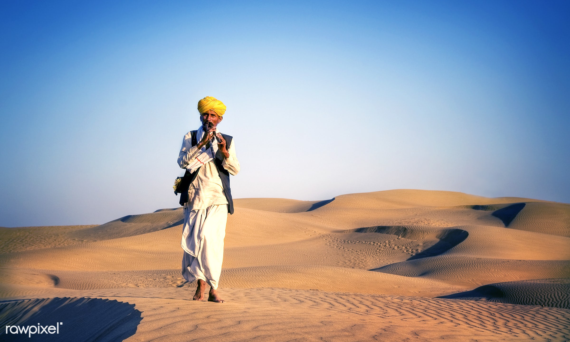Indian man playing wind pipe in a desert. - desert, asia, barefoot, culture, day, exoticism, heat, india, indian, indian...