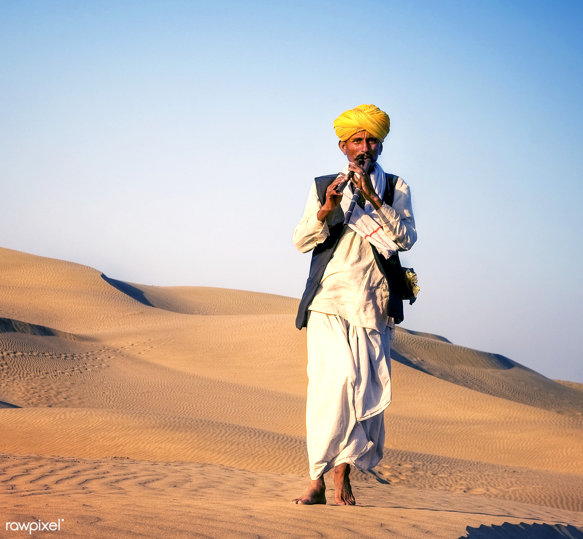 Indigenous Indian man playing wind pipe in a desert. - asia, barefoot, culture, day, desert, exoticism, heat, india, indian...