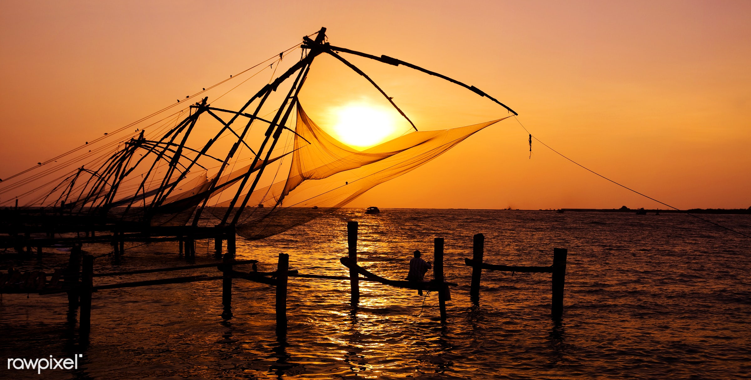 Indian man fishing under the great Chinese nets at Cochin, Kerela, India - dusk, asia, back lit, building feature, built...