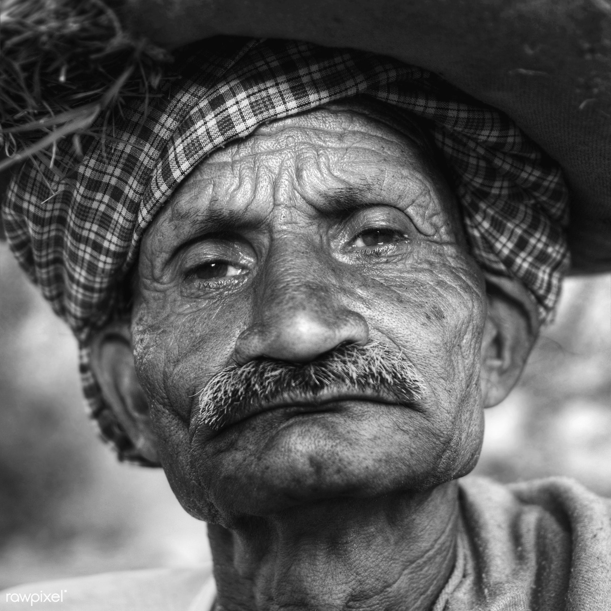 Indigenous senior Indian man looking grumpy at the camera. - carrying on the head, close-up, concepts and ideas, despair,...
