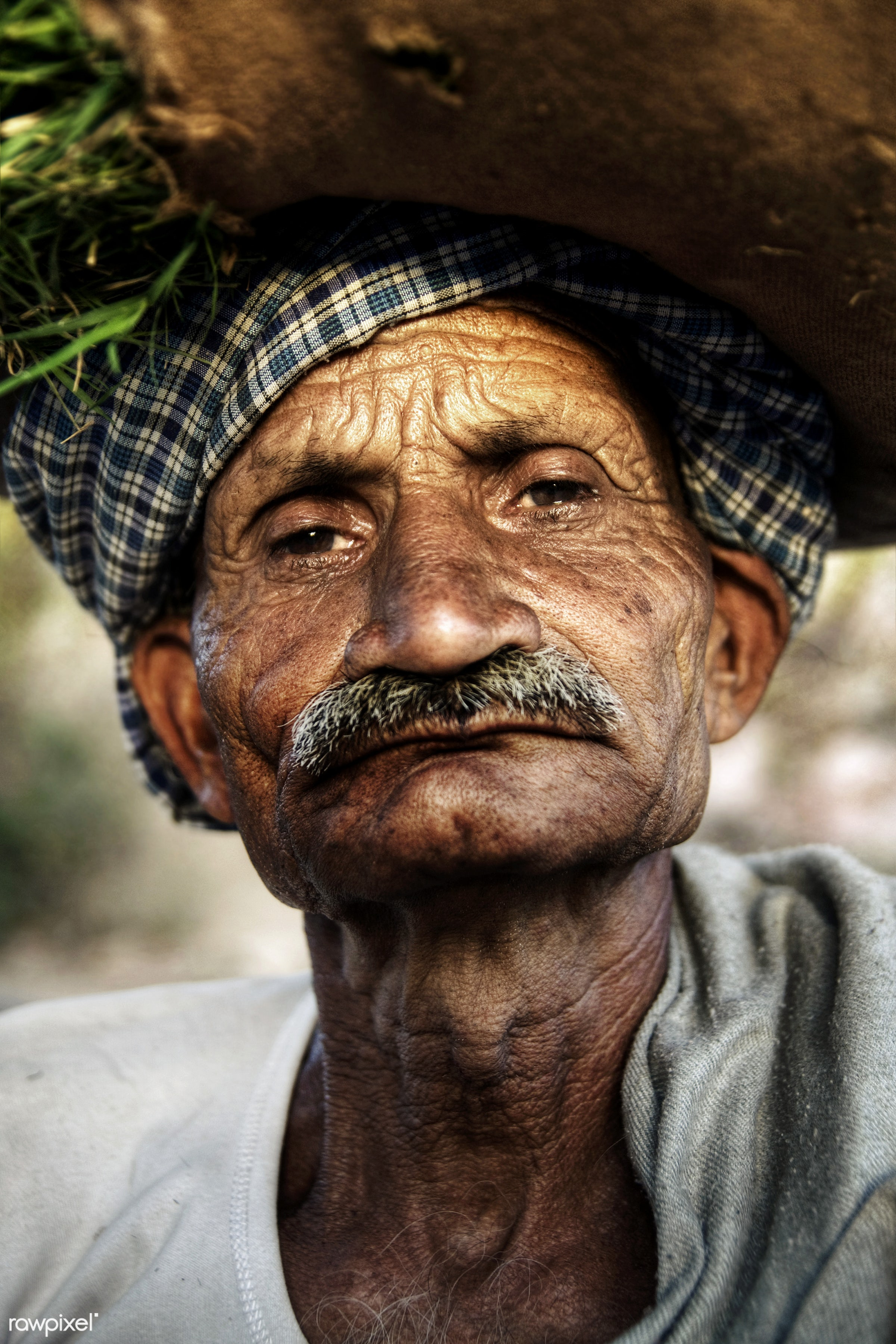 Portrait of a serious Indian man - carrying on the head, close-up, concepts and ideas, despair, farmer, grumpy, hinduism,...