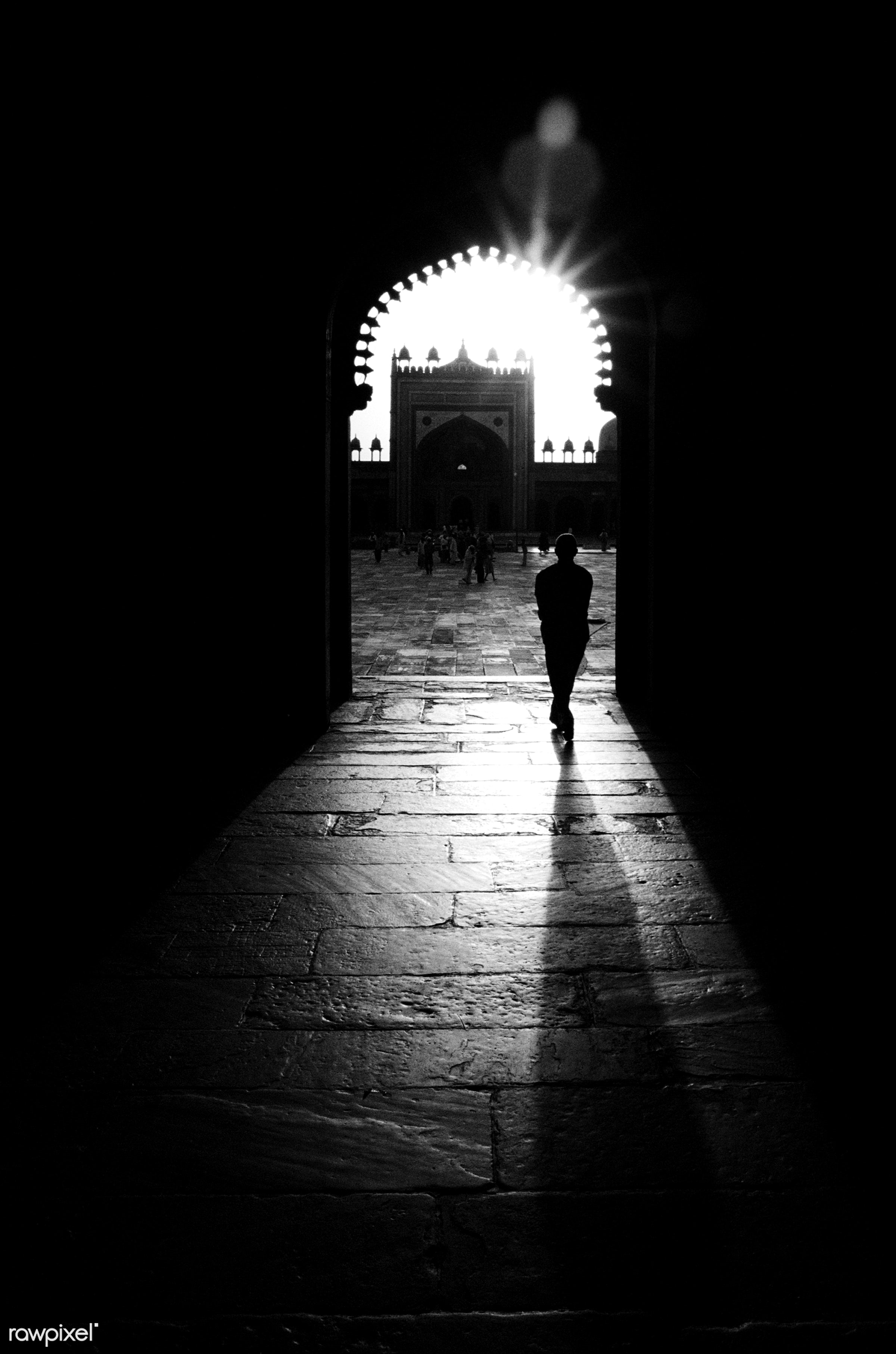 Silhouette of man walking through a mosque. - alam, arch, asia, asian culture, asian ethnicity, back lit, black, dusk,...