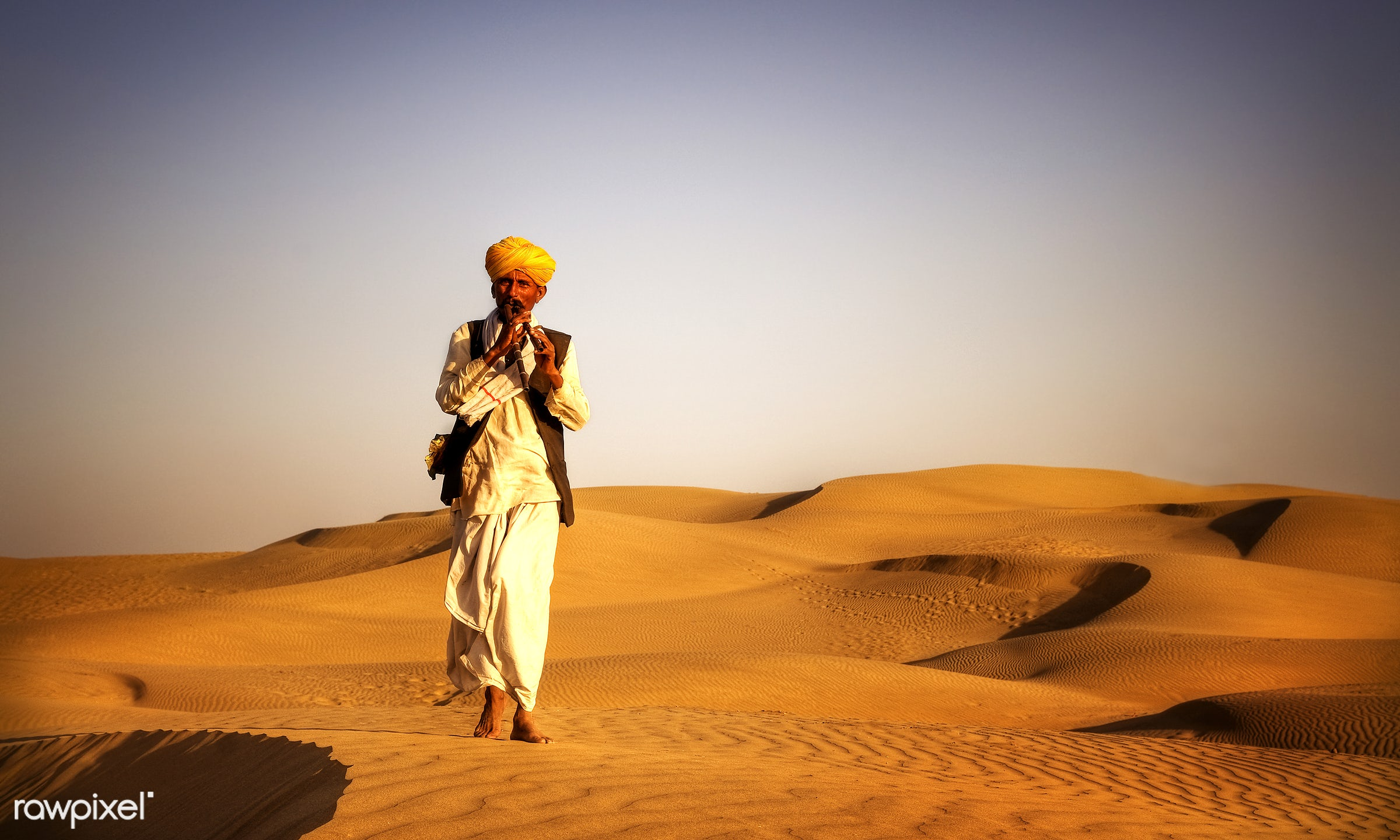 Indian man playing wind pipe in a desert. - asia, barefoot, culture, day, desert, exoticism, heat, india, indian, indian...