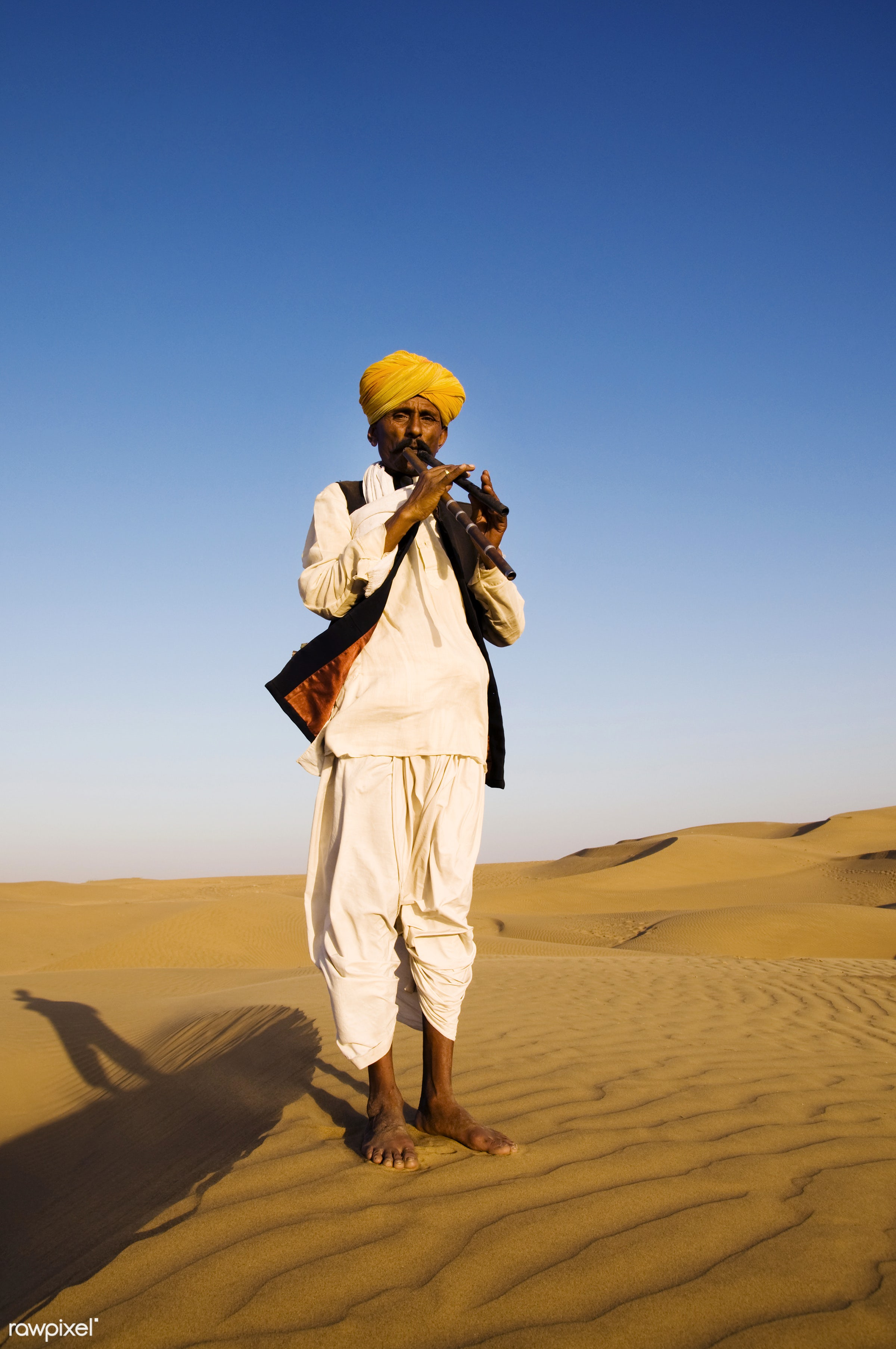 Indian man playing wind pipe in the desert - india, asia, culture, day, desert, exoticism, full length, heat, indian, indian...