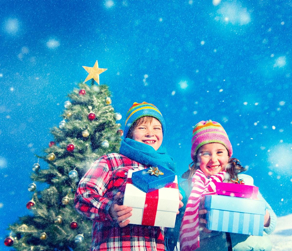 caucasian kids holding gift for christmas