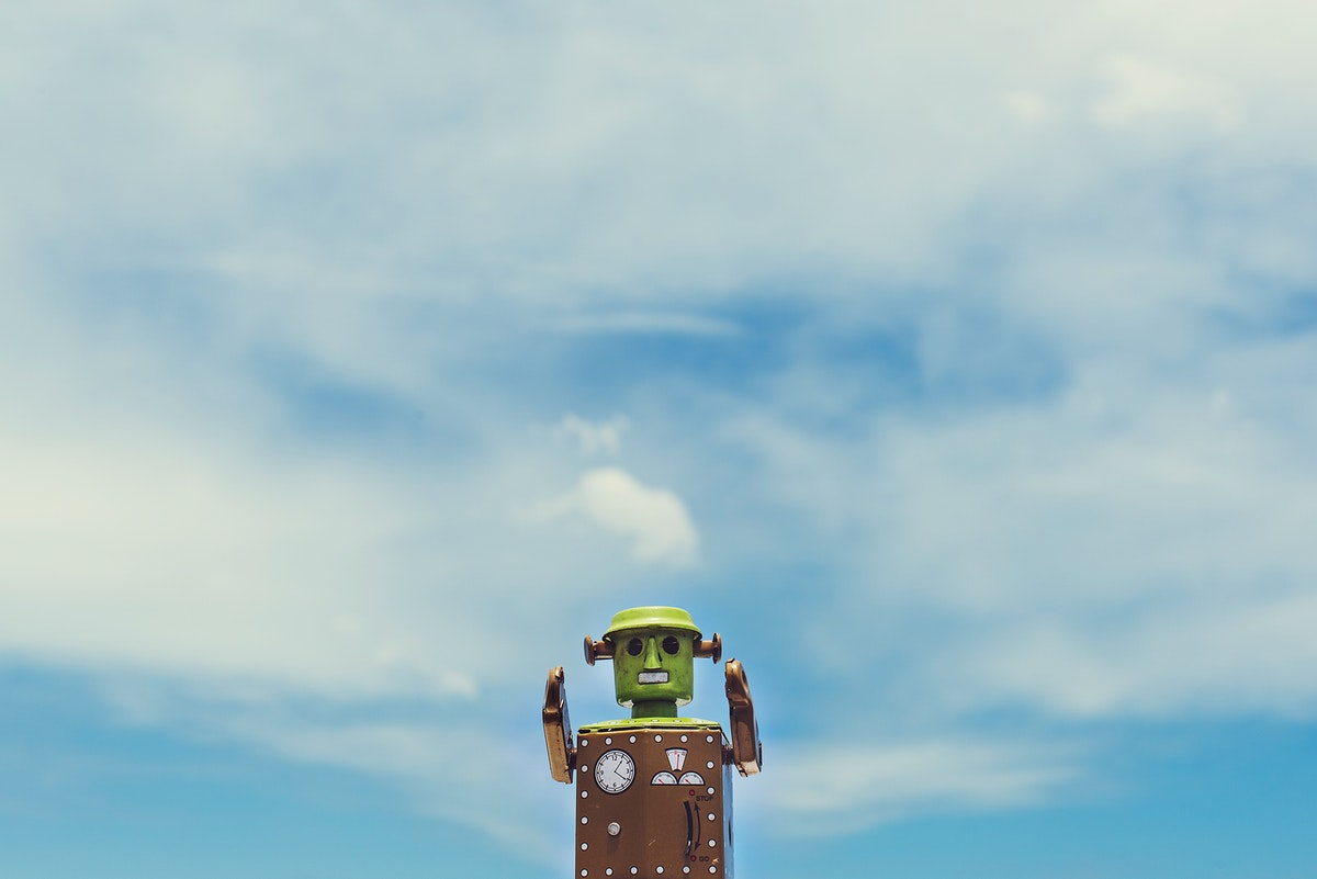 Closeup of robot toy with cloudy blue sky scenic