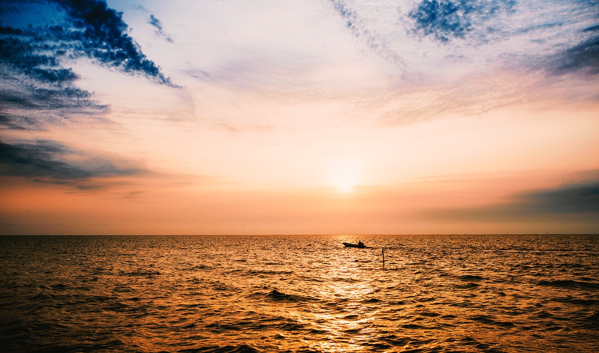Boat in the ocean at sunset