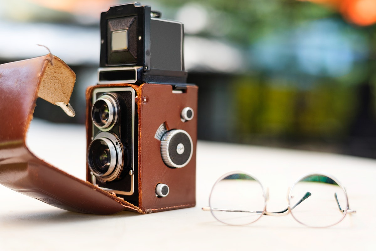 Vintage camera and glasses on the table