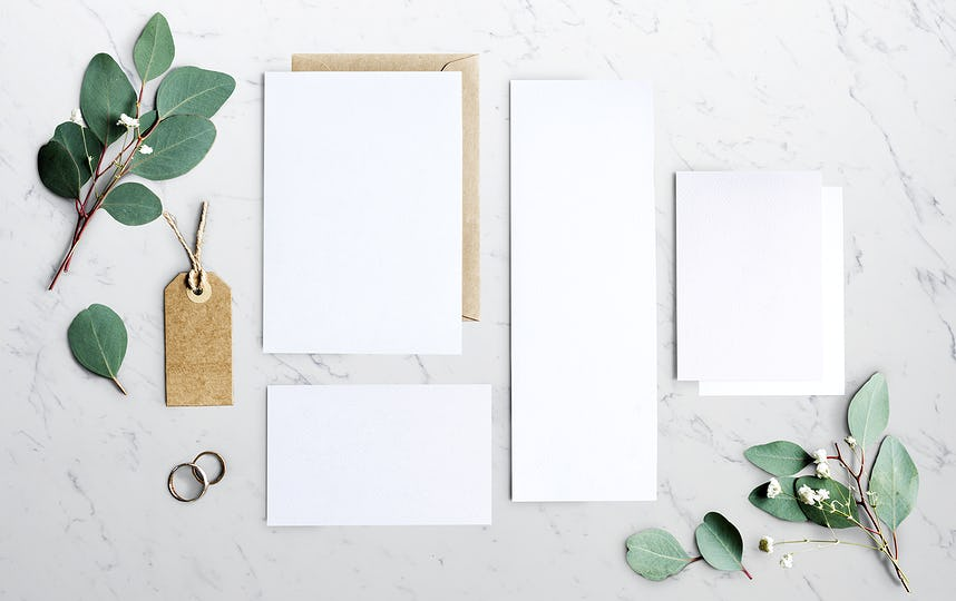 Blank Papers Laying on Marble Table With Leaves Decoration