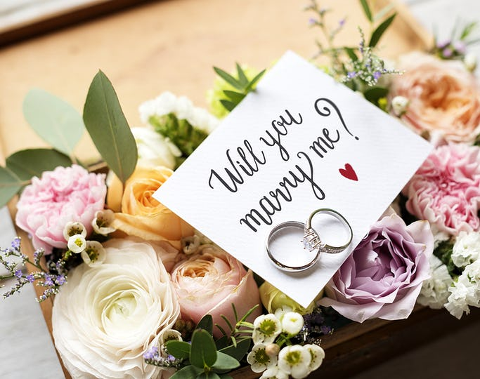 A Surprise Marriage Proposal with Will You Marry Me Card and Rings on Flowers Bouquet Present Love