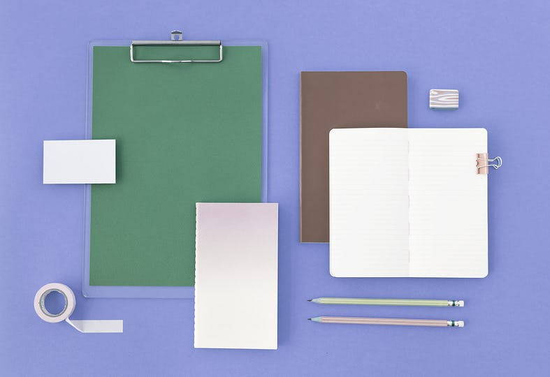 Open Blank Notebook and Stationery on Purple Background