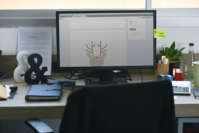 Computer Screen Showing Graphic Deer Design on Office Table Working