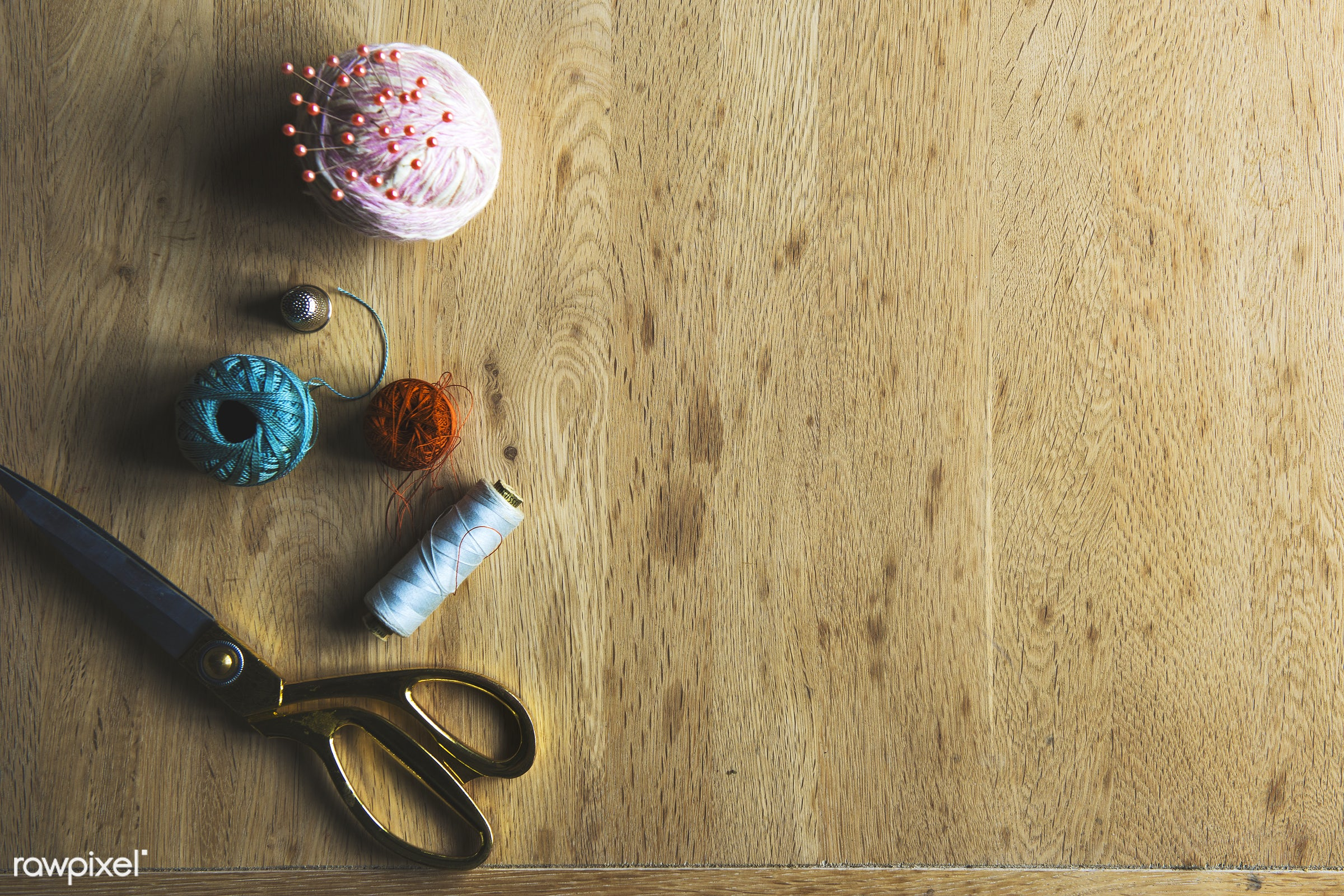 Sewing accessories on a wooden workspace - sew, craft, clothing, cotton yarn, roll, tools, accessory, cloth, thread, tailor...