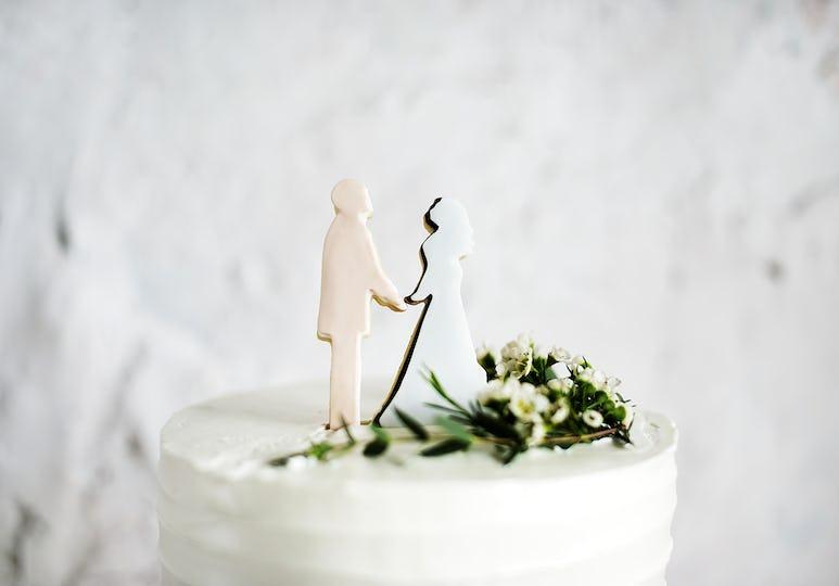 Closeup of groom and bride wedding cake topper