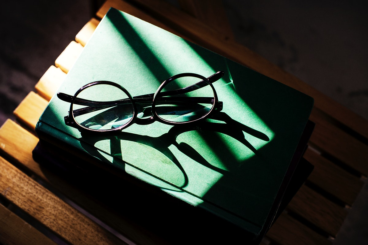 Sunlight hitting a pair of glasses on a book