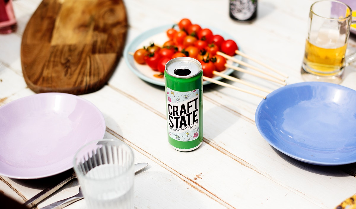 Beer can on wooden table with dishes