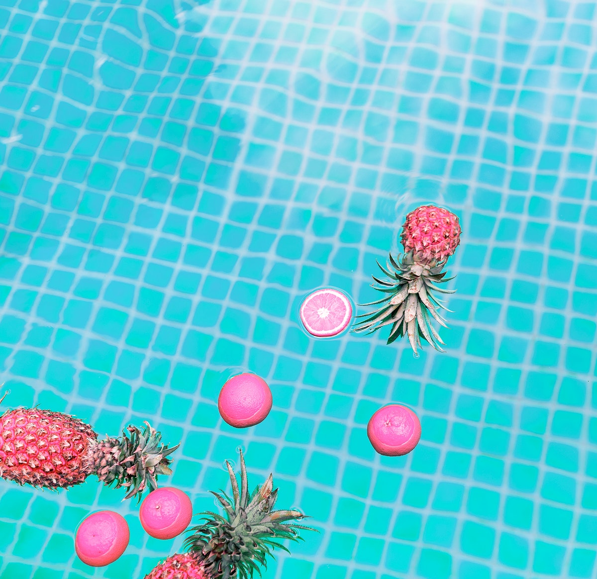 Aerial view of pineapple and oranges floating in a swimming pool