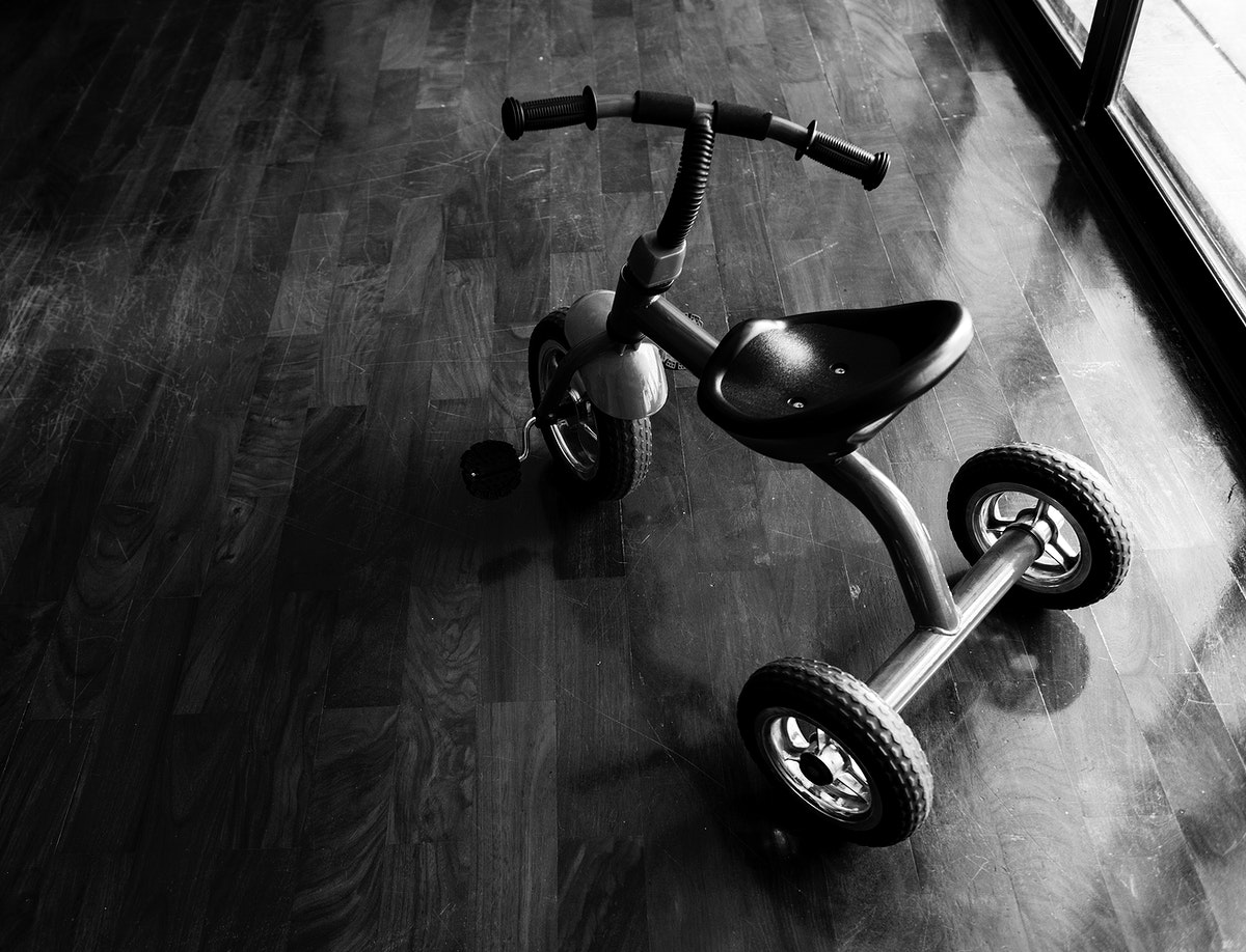 Kid bicycle on the wooden floor grayscale