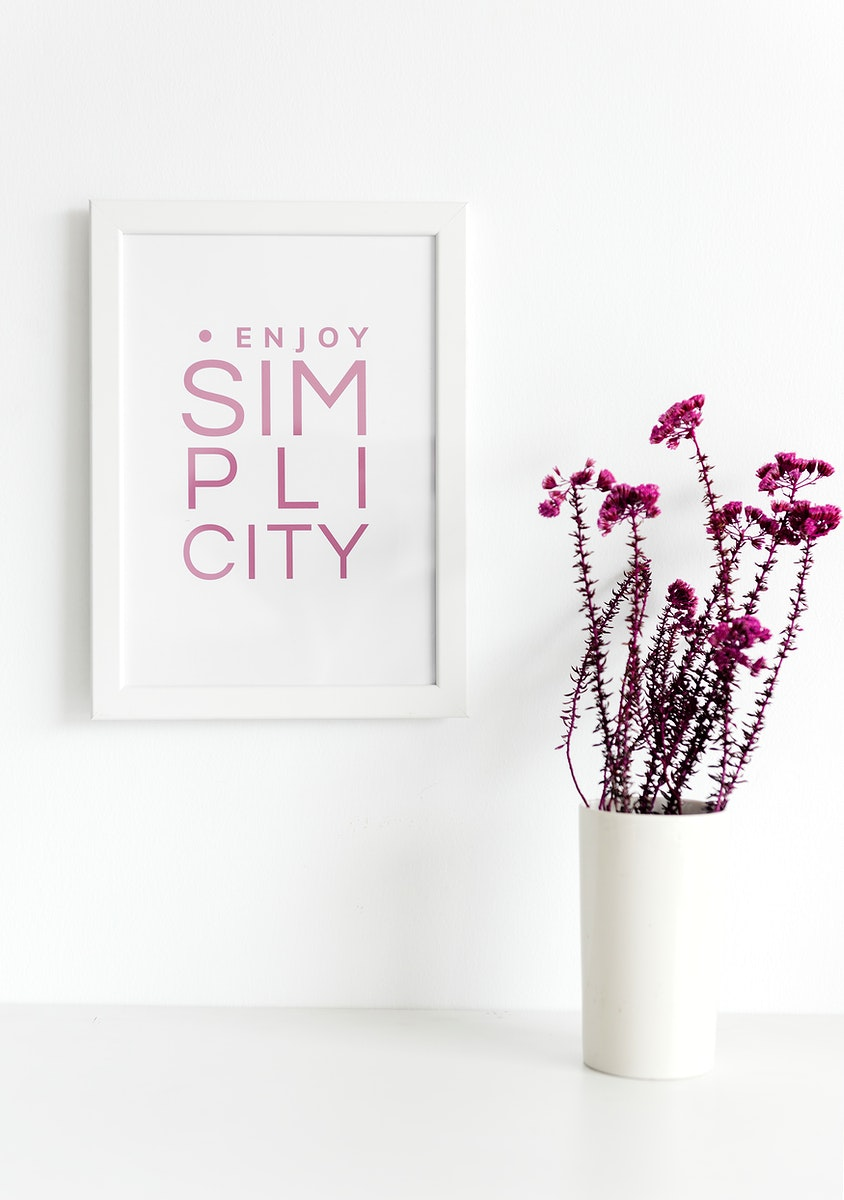 Closeup of pink flowers in white vase with photo frame on wall