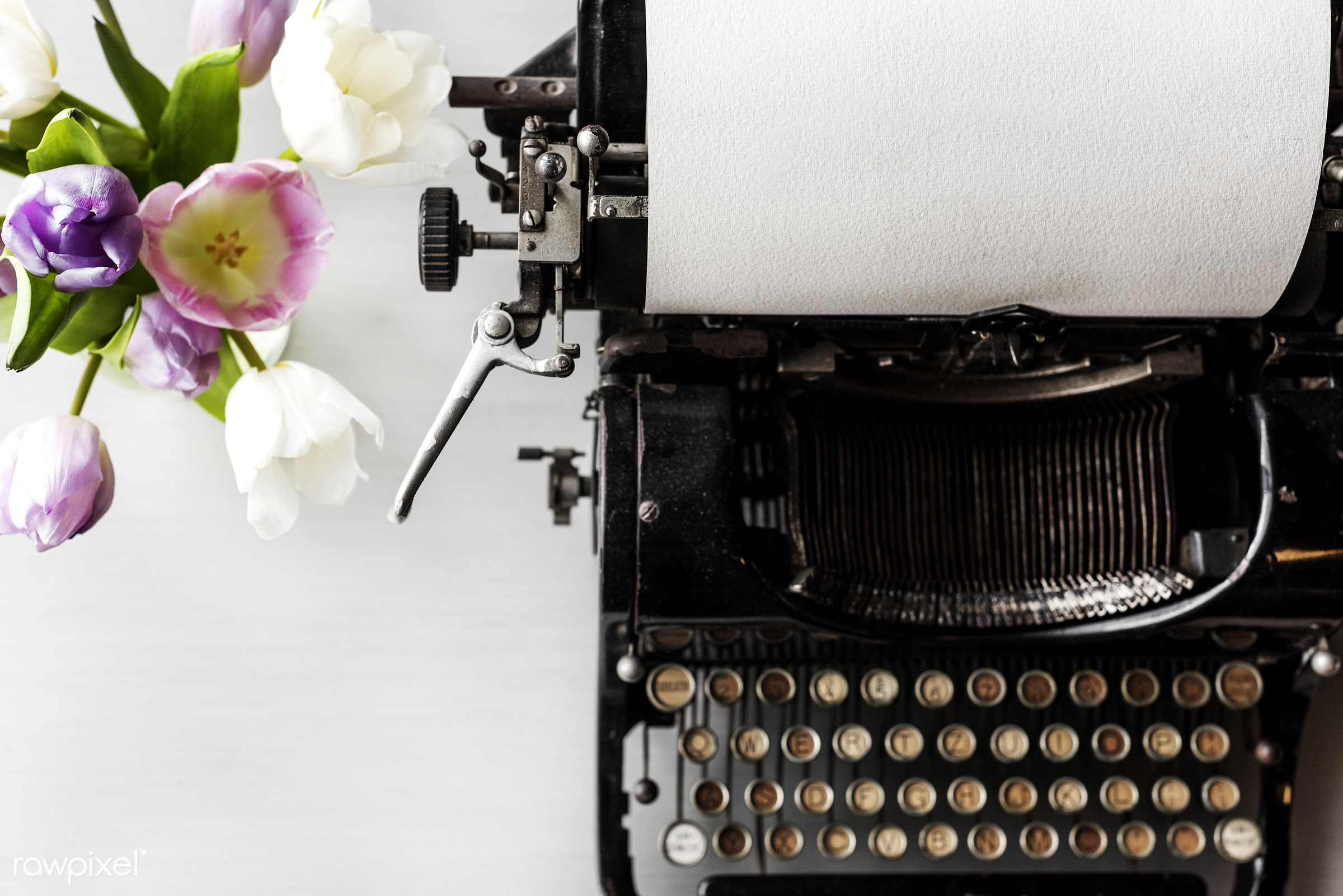 Old typewriter on white tabletop - aerial view, antique, attach, attached, classic, closeup, equipment, flat lay, flower,...