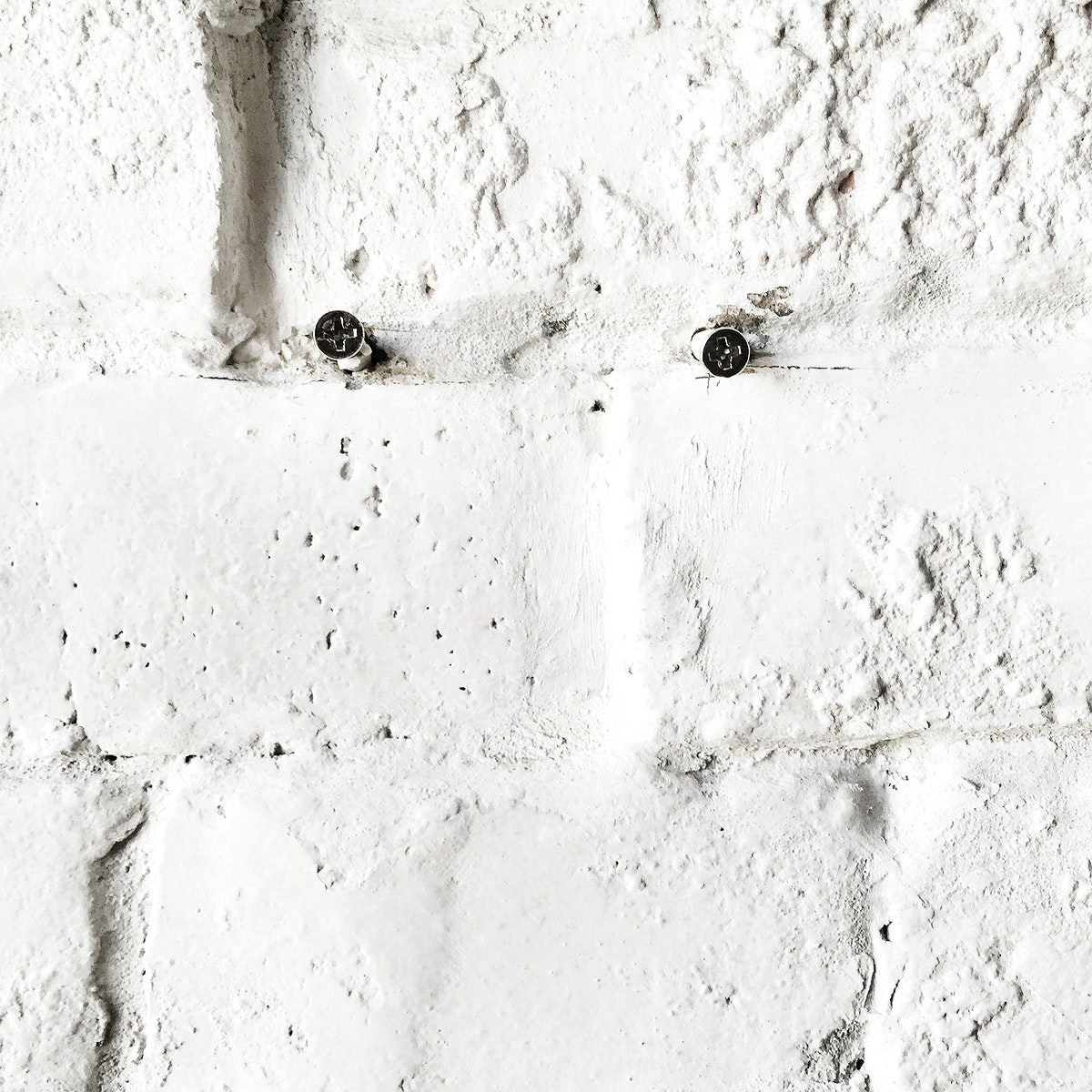 Closeup of screws on concrete white brick wall