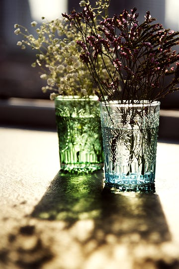 Closeup of flowers in glass vases on wooden table