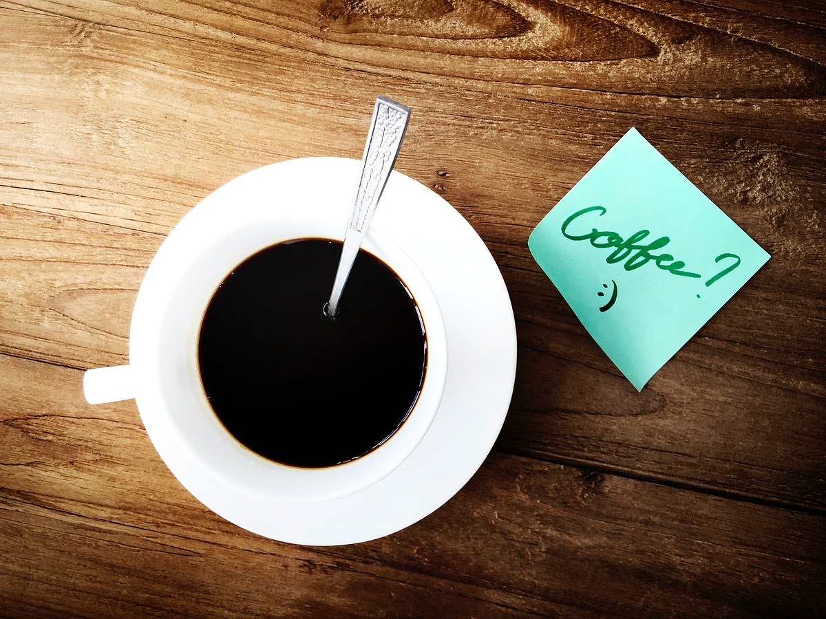Aerial view of coffee cup on wooden table with sticky note