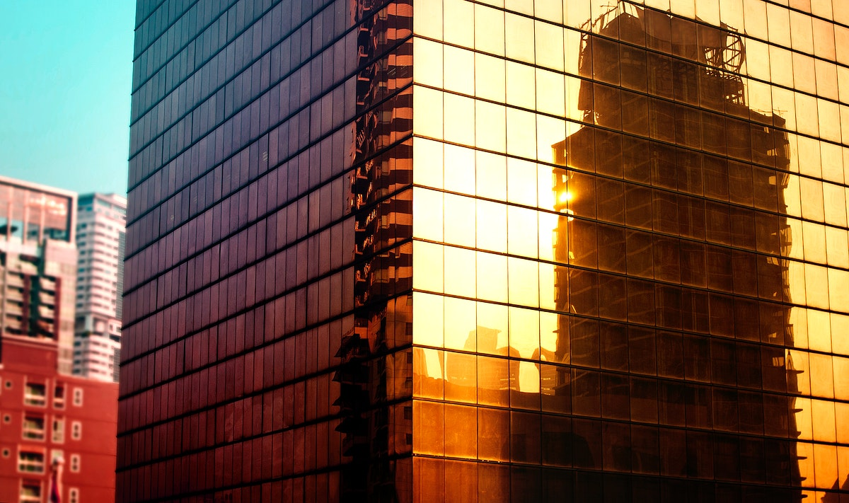 Reflection of metro city buildings on glass mirror exterior