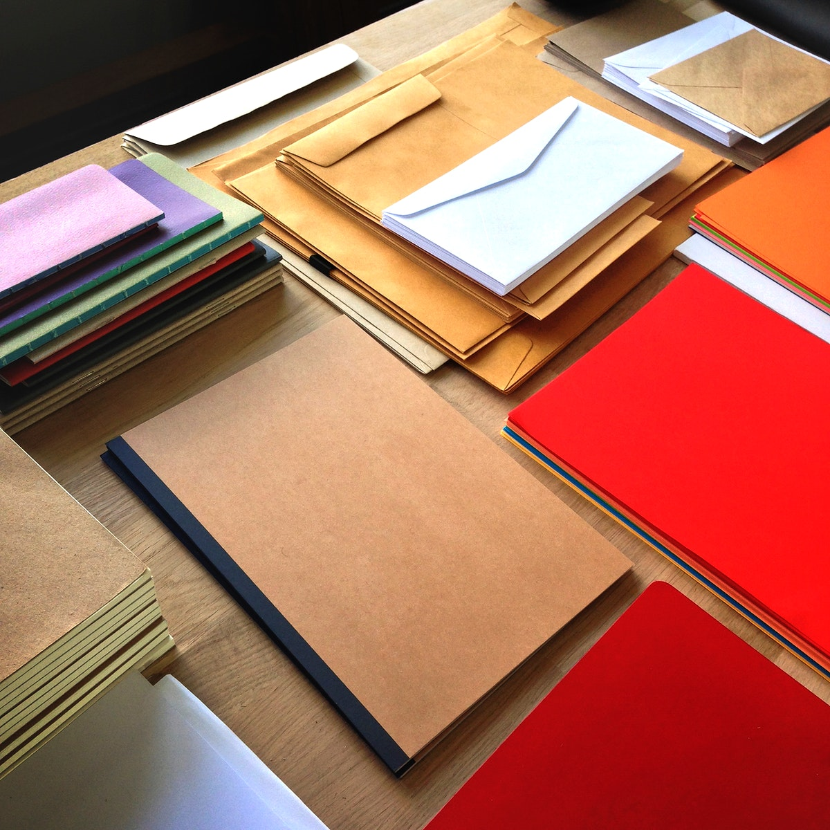 Closeup aerial view of notepads and envelopes letters on wooden table