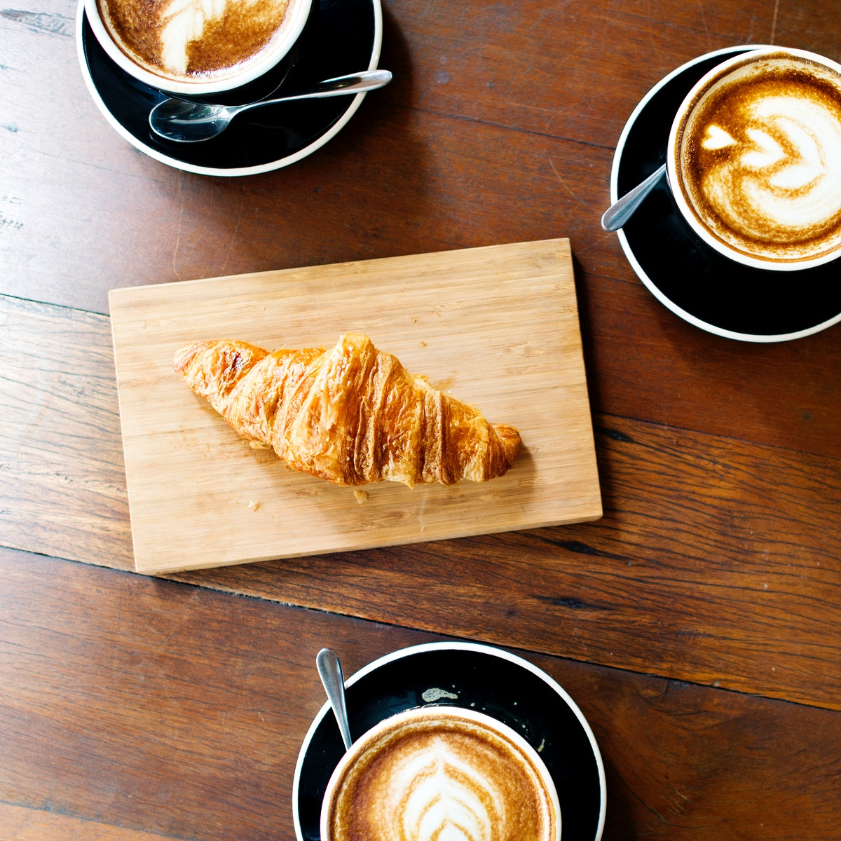 Aerial view of coffee cups and croissant on wooden table
