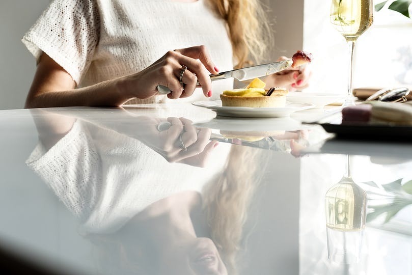 Closeup of woman eating tart dessert in cafe with reflection on table
