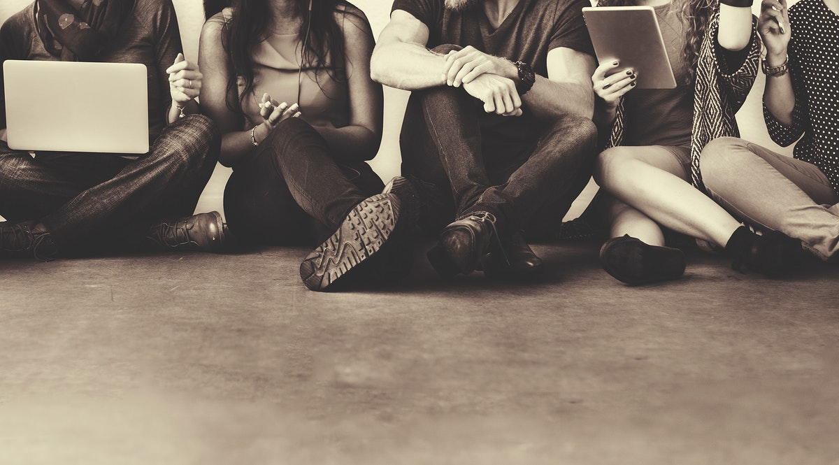 Group of diverse friends sitting on the floor using digital devices sepia