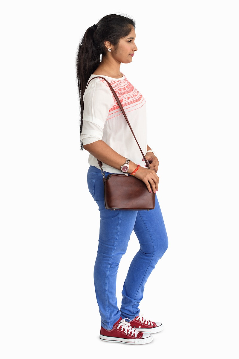 Casual young woman standing carrying her bag
