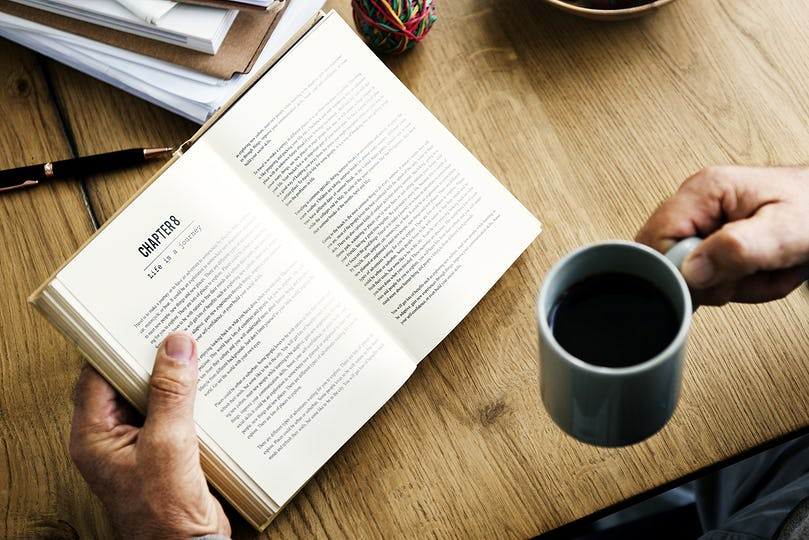 Closeup of hands holding open novel and coffee cup