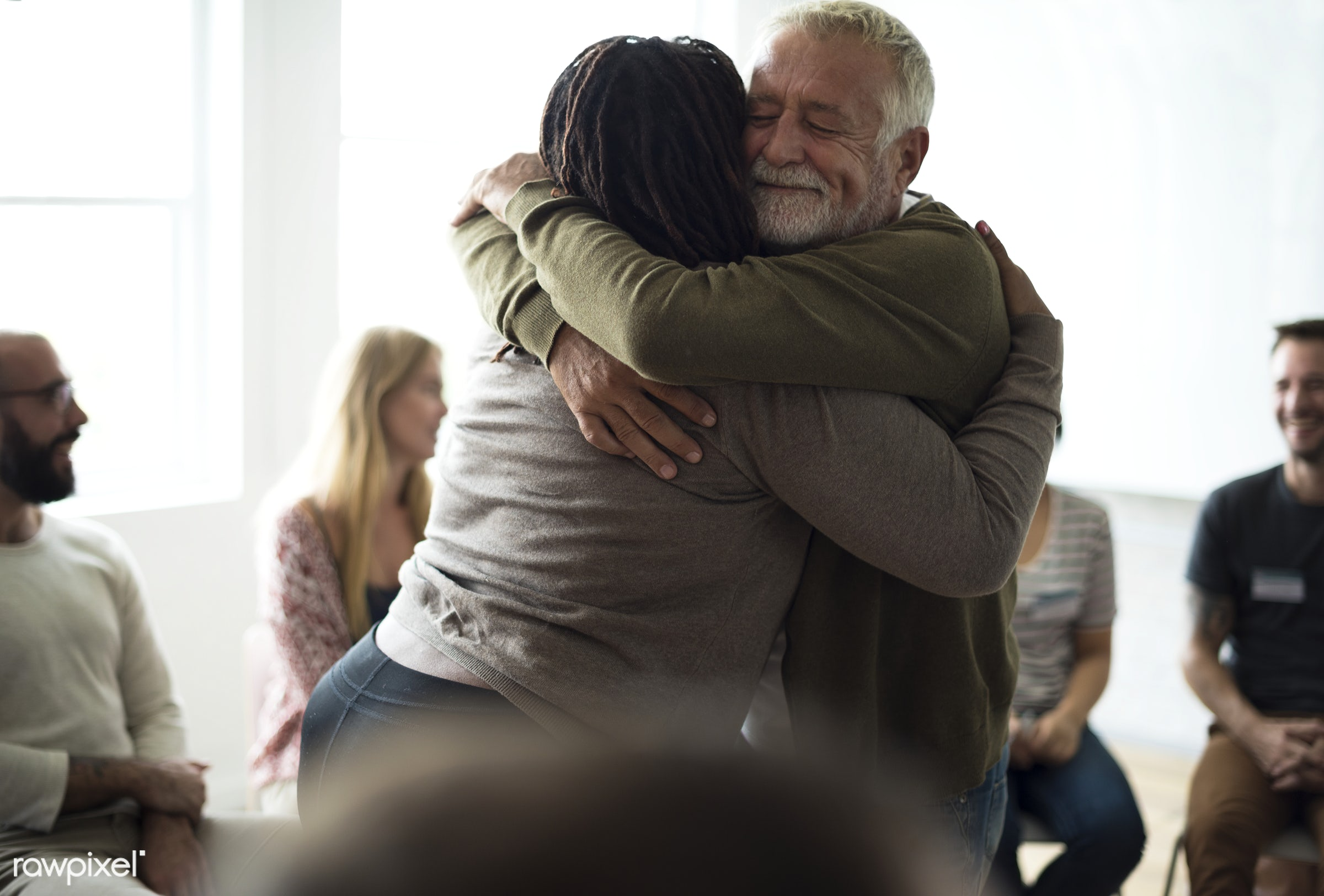Senior man hugging woman in support group - person, collaboration, chairs, people, together, caucasian, help, friends, girl...