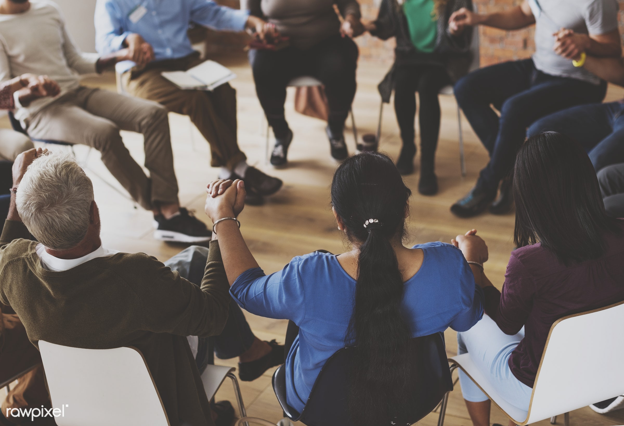 Diverse group of people holding hands in support group - person, collaboration, african ethnicity, holding, chairs, circle,...
