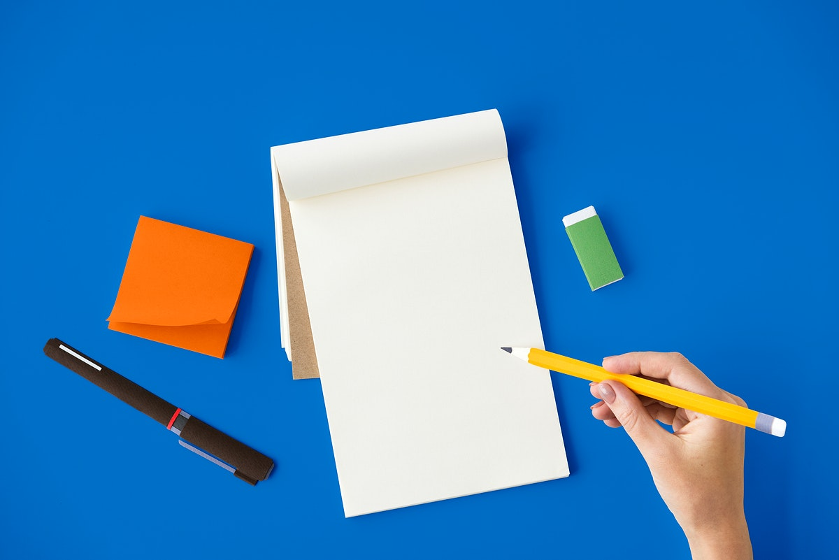 Aerial view of hand holding pencil write notepad on blue table