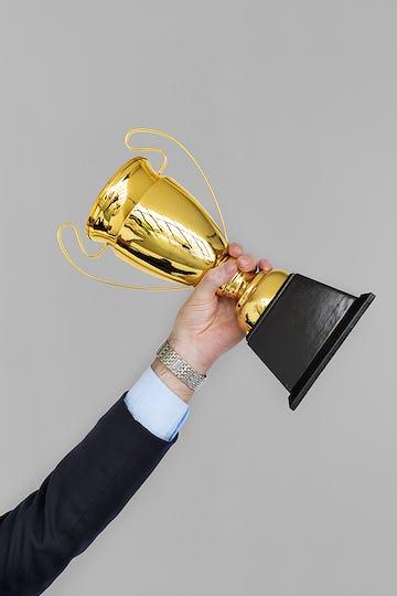 Human Hand Holding Trophy Reward Success
