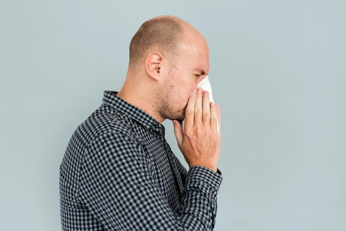 Man sneezing blowing nose sickness